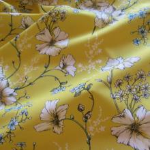 Tessuto di cotone giallo con fiori bianchi e azzurri