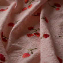 Light pink broderie anglaise cotton fabric with embroidered flowers