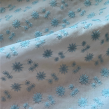 White coton fabric with blue embroidered flowers